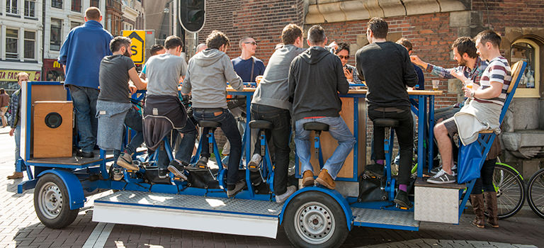 A group of 15 men sit around table on a beer bike, drinking and talking