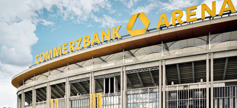 The outside of the football stadium in Frankfurt, looking up at a huge yellow sign that reads 'Commerzbank Arena'