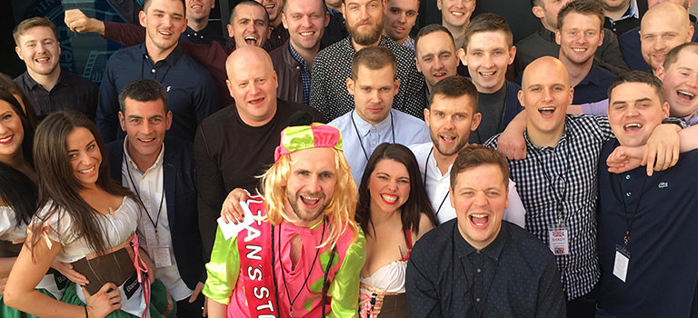 A large group of men on a barcrawl with a few women dressed in costume