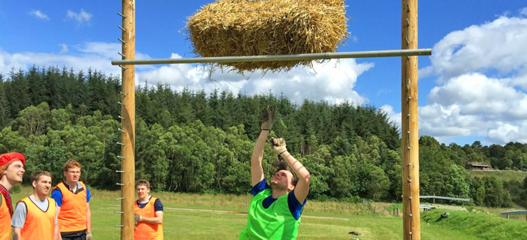 A man throwing a bale of hay in the air
