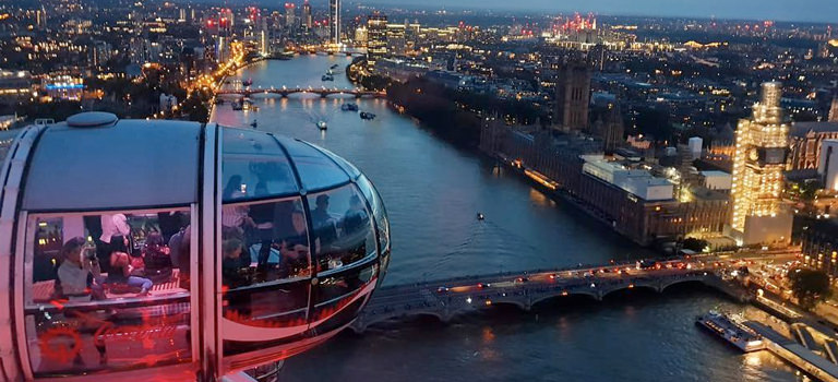 A pod of the London Eye filled with people, looking out over the city