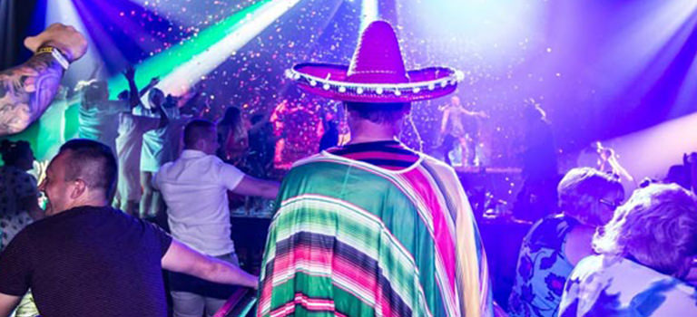 A man wearing a sombrero in a club