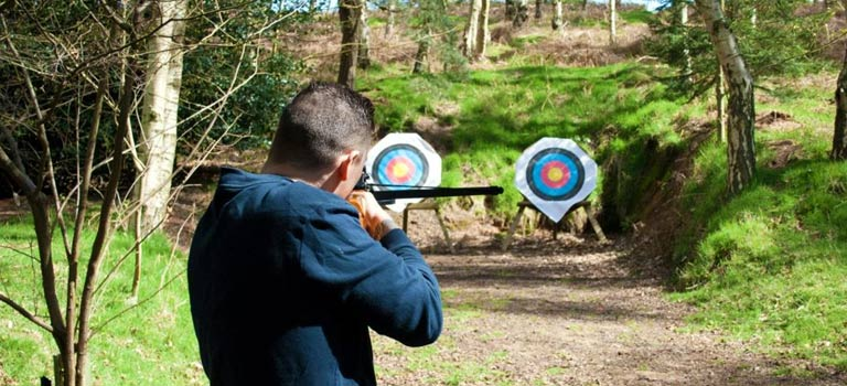 A man practicing target shooting in a wood