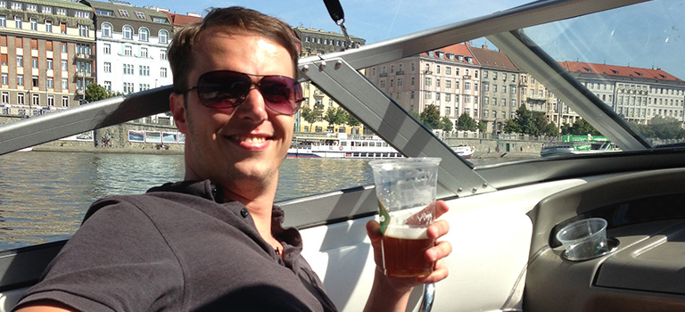 A man on a boat in Prague with a pint