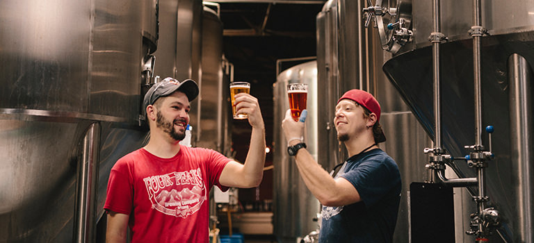 Two men holding up pints of beer in a brewery