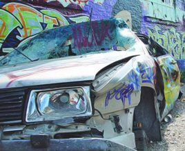 A vandalised car in front of a graffiti wall