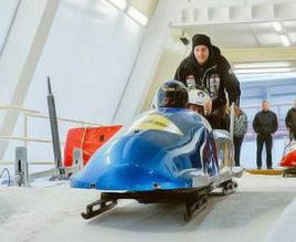 Close up of people in a blue bobsleigh at the top of a track, with a man stood behind and pushing them