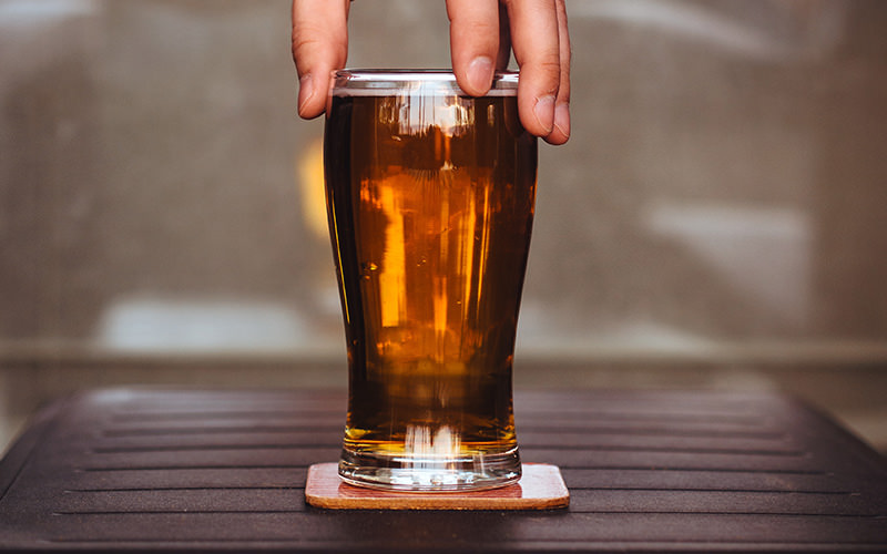 A man's fingertips holding the rim of a pint