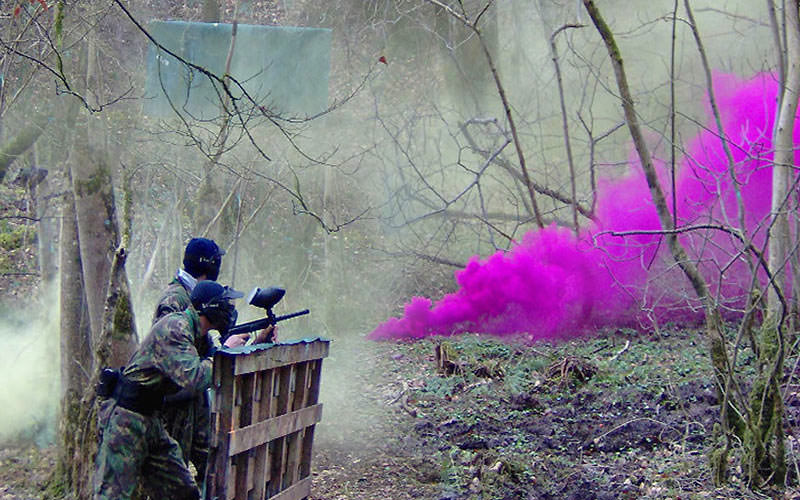 Some men playing paintball, whilst a purple paint grenade goes off