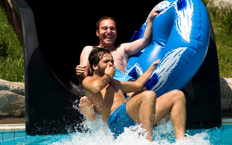 Two men coming down from a water flume
