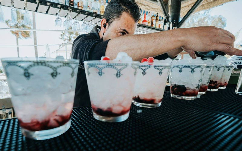 A barman pouring drinks at the bar