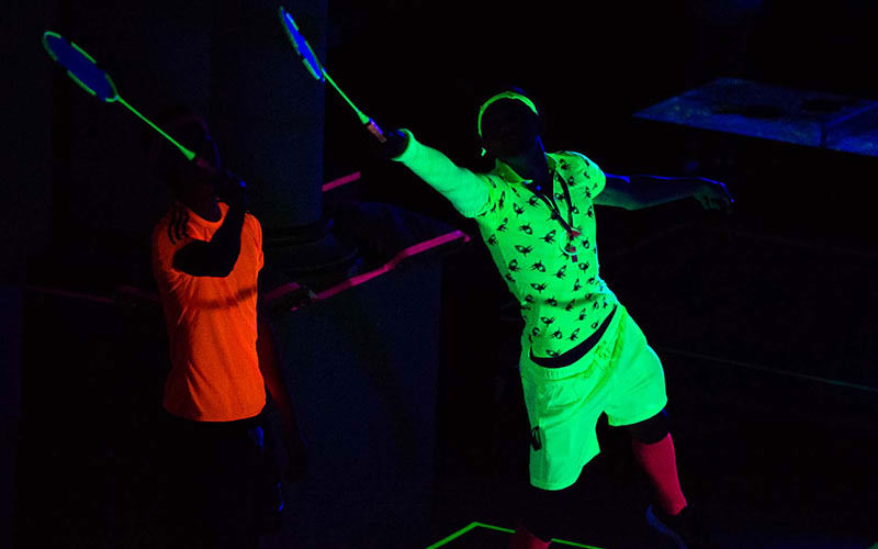 Two men playing badminton and wearing neon clothing under UV lighting