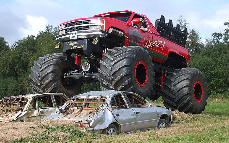 A monster truck crushing two cars