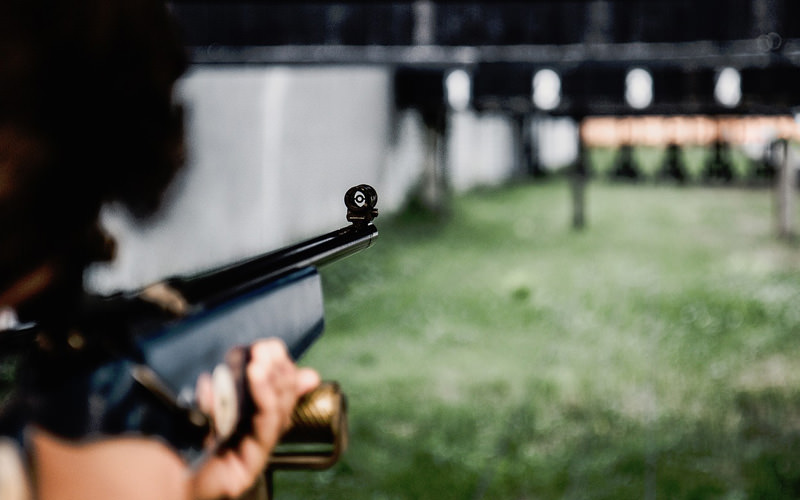 A man firing a gun in a shooting range