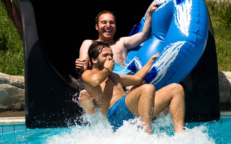 Two men coming down a flume into a a swimming pool