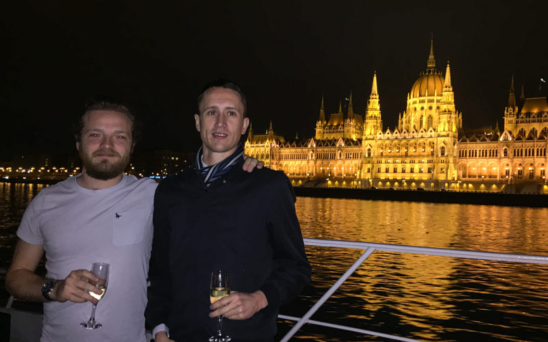 Two men in front of a building in Budapest, holding glasses of Champagne