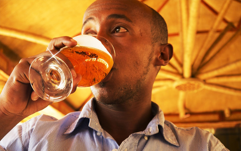 A man holding a beer to his lips