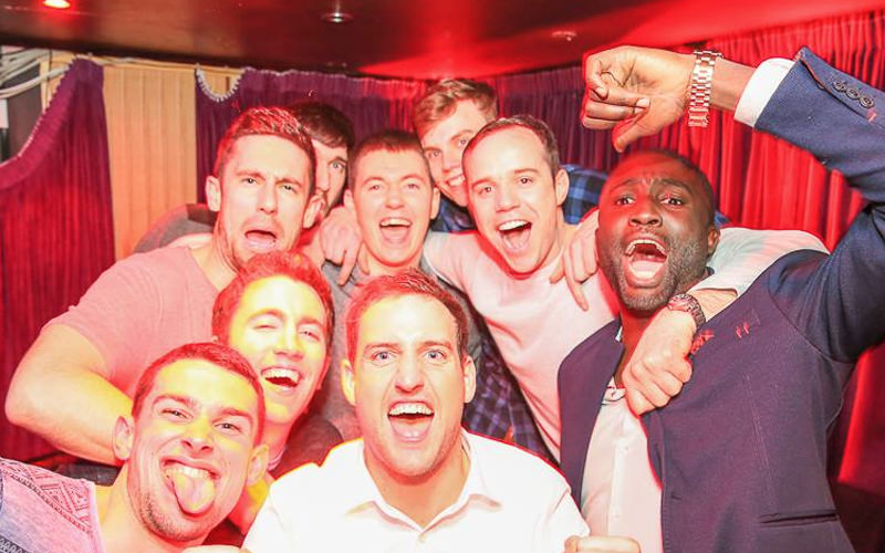 Nine lads celebrating in a room with red curtains