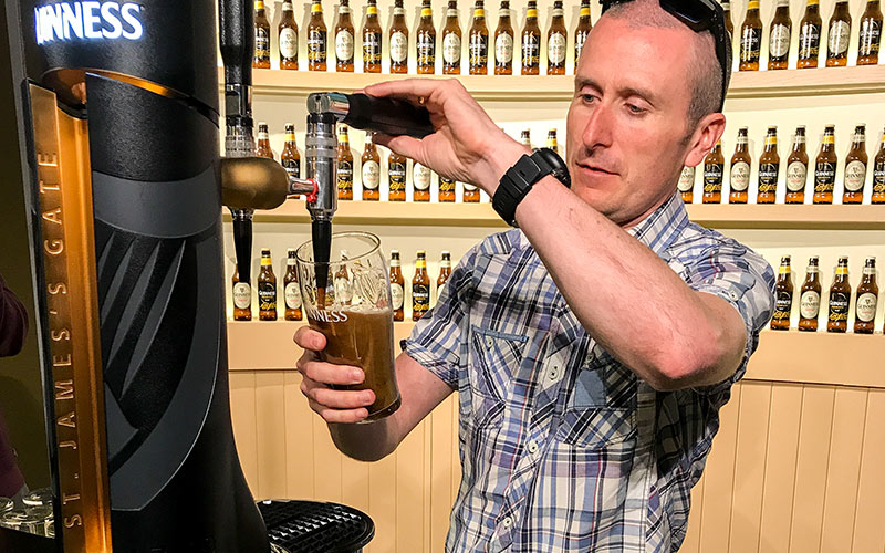 A man pulling his own pint of Guinness in the Guinness Storehouse, Dublin