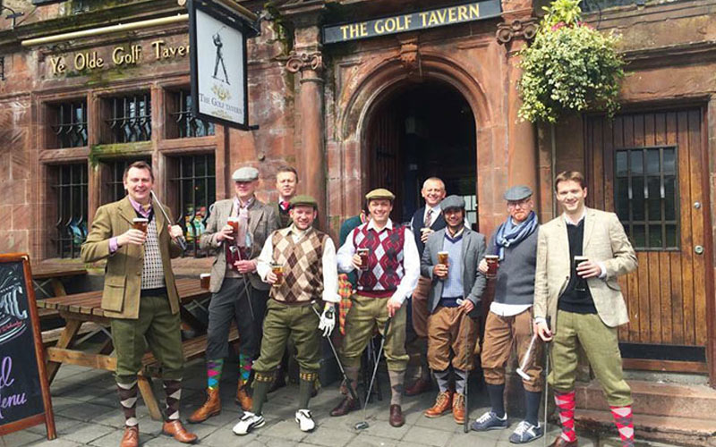 A group of men outside a pub in Edinburgh, dressed for pub golf