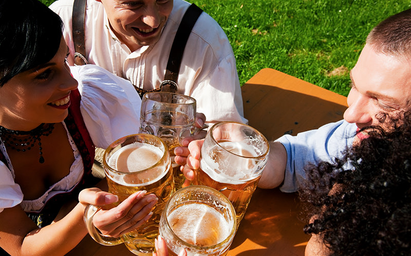 Four people drinking steins and holding them together over a table