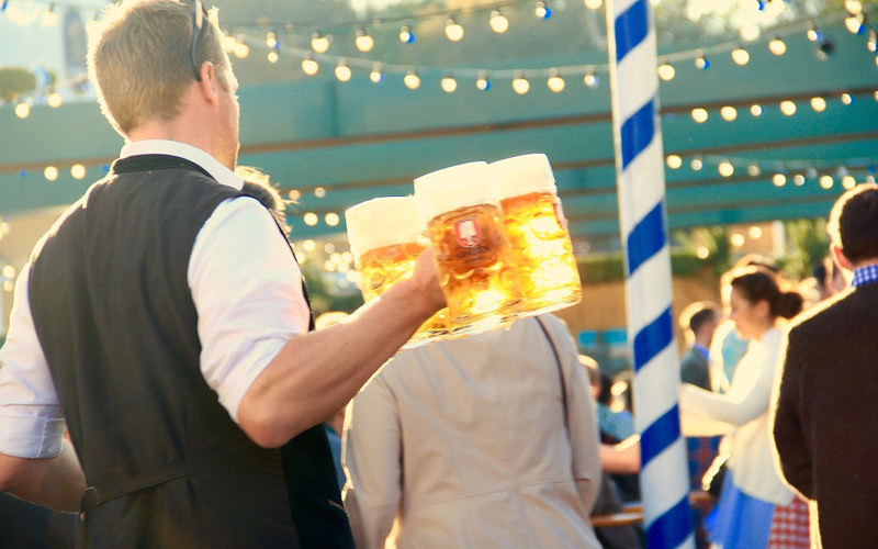 A barman carrying four large steins at an outdoor bar