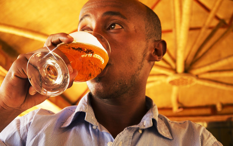 A man drinking a small beer out of a glass
