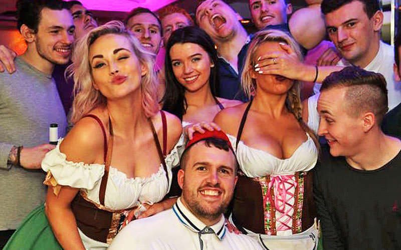 A group of stags with some Bavarian beer maids on a bar crawl