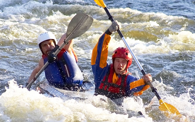 Two men paddling against the white water rapids