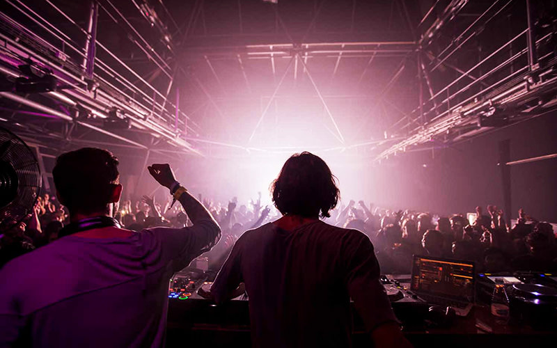 Two DJs performing to a dark room with silouettes of people