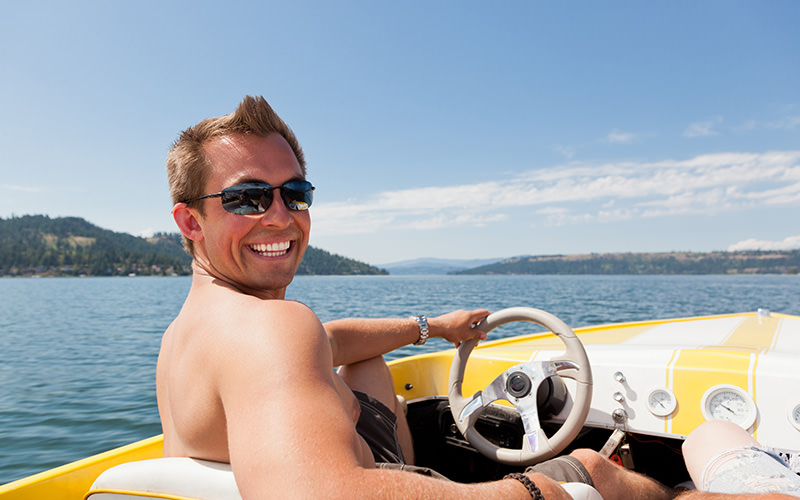 A man driving a speed boat on the sea