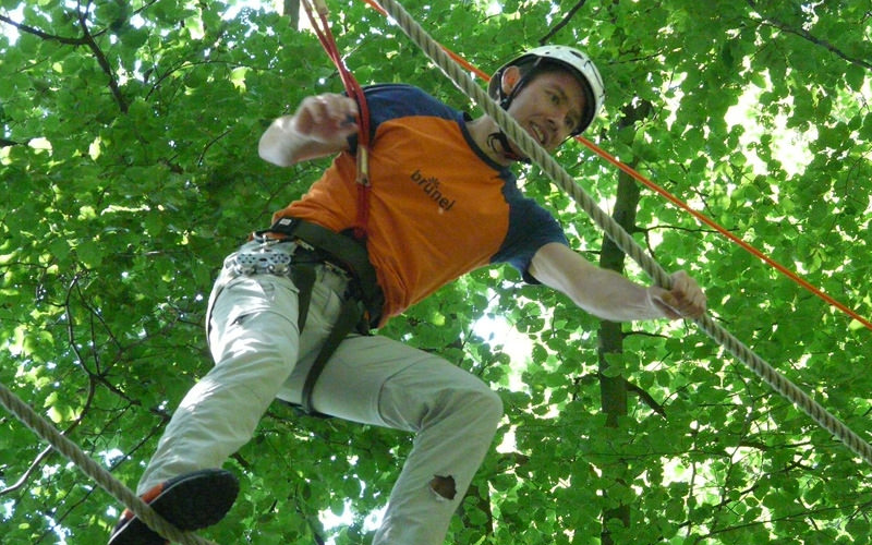 A man doing a high ropes course