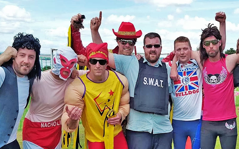 Seven men dressed up in wrestlers outfits on a stag do
