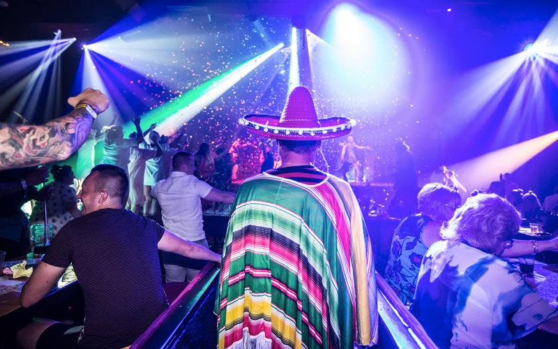 A man heading into a club, wearing a sombrero