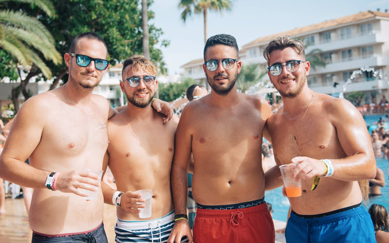 Four men wearing swimming shorts by the side of the pool, holding their drinks