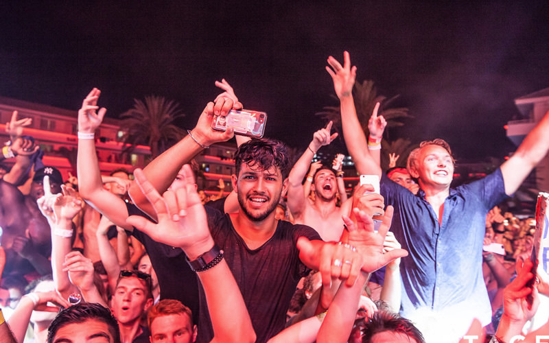A group of men holding their hands to the air at an open air party in Magaluf