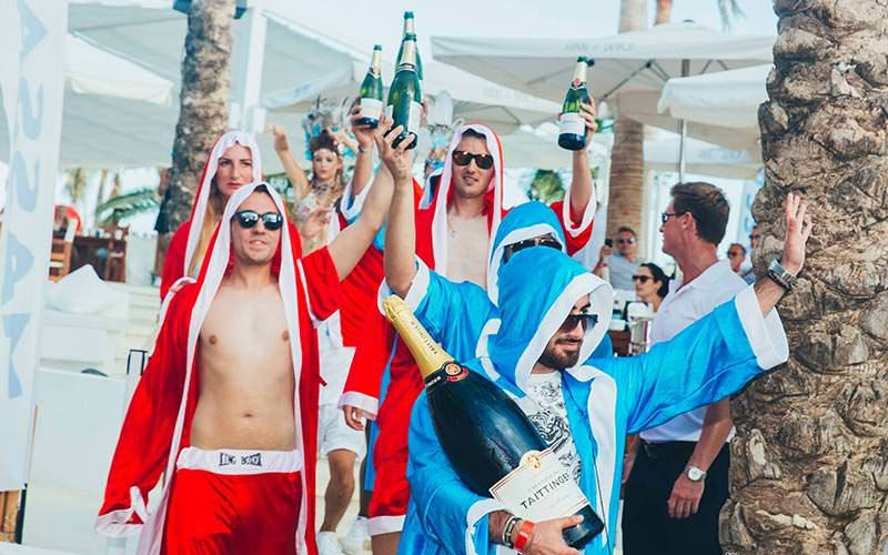 Some stags wearing boxing robes and holding bottles of Champagne