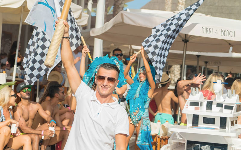 A man holding his arm in the air and some girls behind holding racing flags