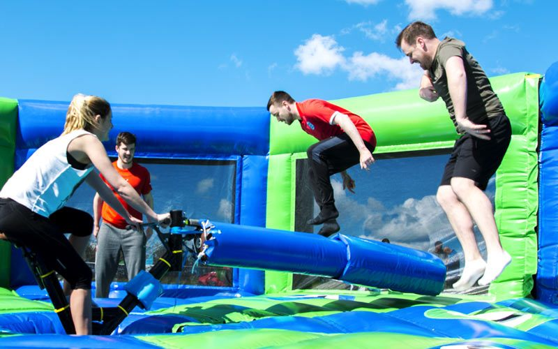People jumping over an inflatable obstacle at the Geordie Games