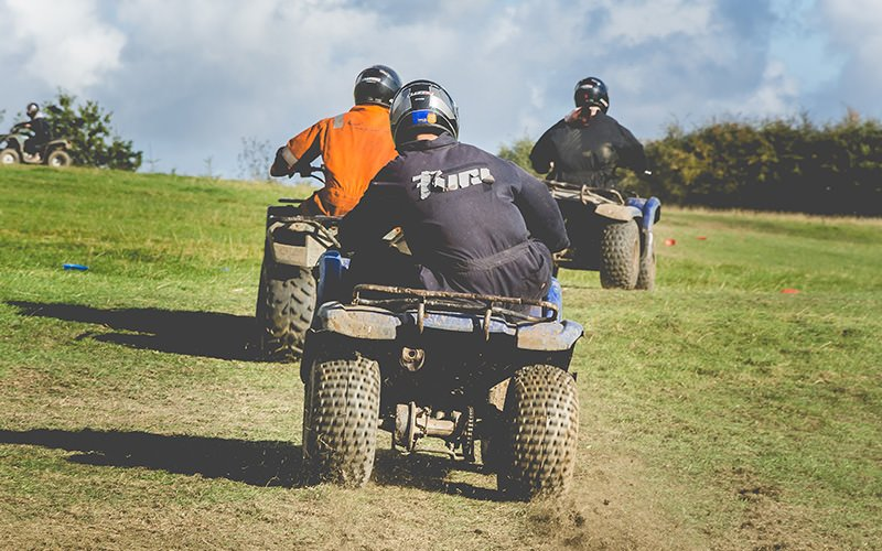 A group of men on quad bikes in a muddy field