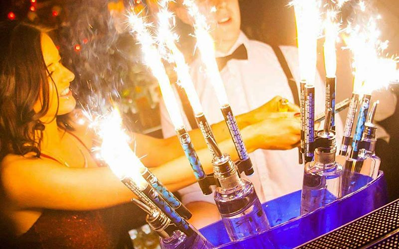 A woman in a nightclub serving drinks with sparklers