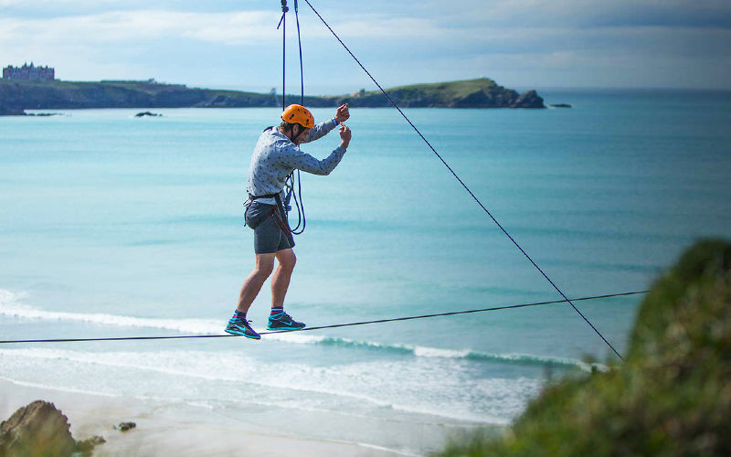 A man doing a tightrope walk in Newquay, with the stunning scenery as a backdrop