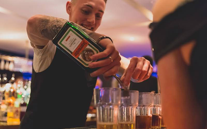 A barman pouring Jagermeister into glasses of Red Bull