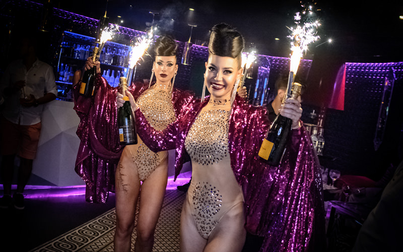 Some women dressed in sparkly leotards with pink capes on, holding flaming bottles of prosecco
