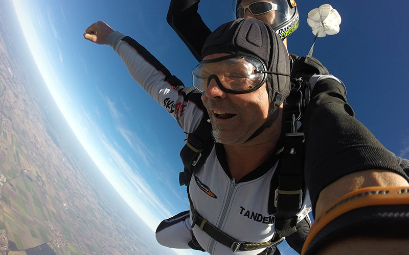 Two people sky diving, with a parachute opening out above them