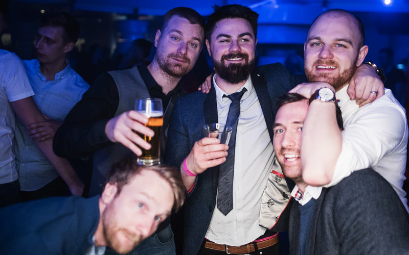A group of men in a club, holding drinks