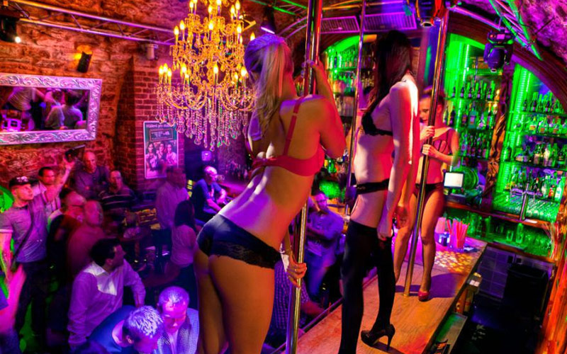 Three strippers in their underwear, dancing on the bar with men watching
