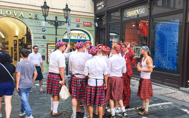 A group of stags dressed in kilts, in a square in Prague