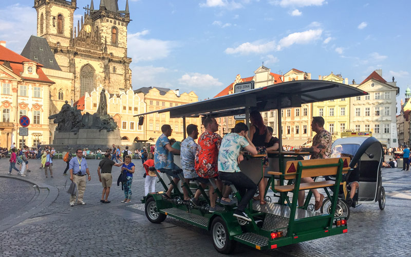 Some men on a pedi bus in Prague Old Town square