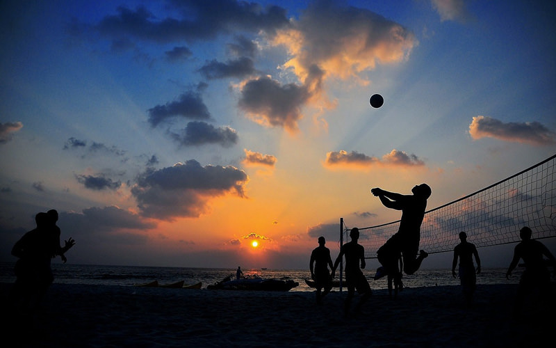 A group of people playing beach volleyball at sunset